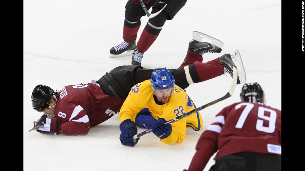 Swedish hockey player Daniel Sedin, in yellow, vies with Latvia's Sandis Ozolinsh on February 15.