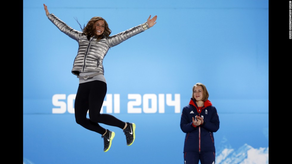 U.S. silver medalist Noelle Pikus-Pace jumps in the air as Great Britain's gold medalist Elizabeth Yarnold looks on during the women's skeleton medal ceremony on Saturday, February 15.