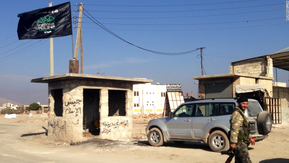 The checkpoint at the entrance to the Syrian town of Addana is where members of the Islamic State in Iraq and Syria, or ISIS, used to dump the bodies of those they had executed to remind others of the consequences of violating their harsh rules. Now that ISIS has left the town, a flag representing the Islamic Front flies over the checkpoint.