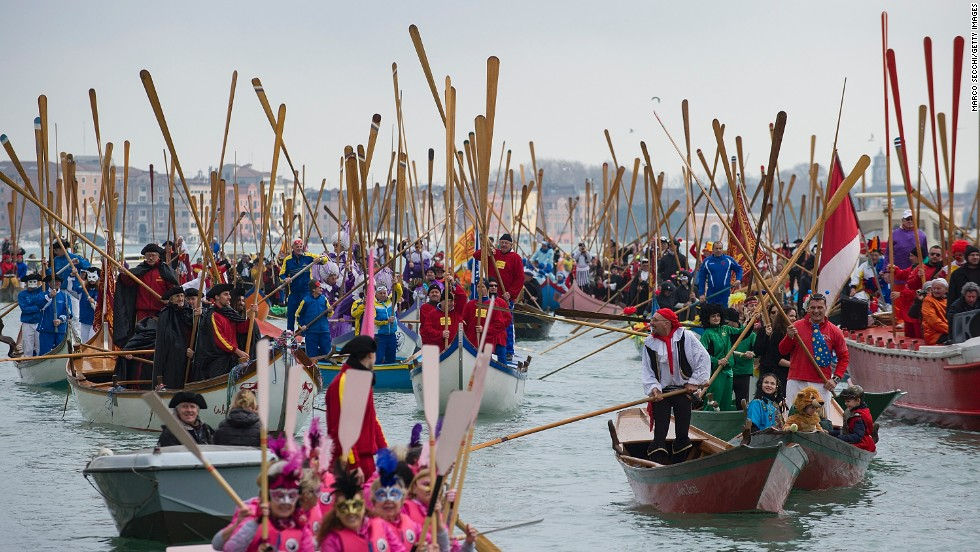 Rowers lift their oars in a sign of salute ahead of the traditional regatta on the Grand Canal, which officially opens the Venice Carnival, on Sunday, February 16, in Italy.