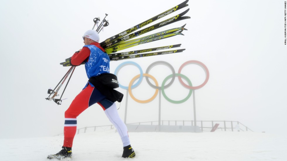 An athlete carries skis through the thick fog that caused event delays and cancellations on February 17.