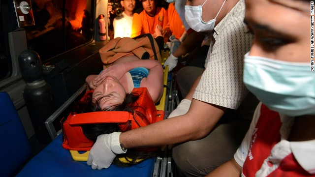 A Japanese scuba diver is carried onto an ambulance from a boat as she arrives in Sanur in Denpasar on the Indonesian island of Bali after being rescued on February 17, 2014. Five Japanese scuba divers were found alive on February 17 clinging to a coral reef in rough waters off the Indonesian resort island of Bali three days after they went missing, officials said.  AFP PHOTO/SONNY TUMBELAKA        (Photo credit should read SONNY TUMBELAKA/AFP/Getty Images)