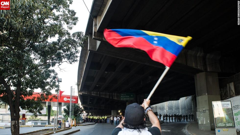 Un estudiante frente a los efectivos de seguridad ondea la Bandera Nacional de Venezuela durante las protestas del 15 de febrero en Caracas.