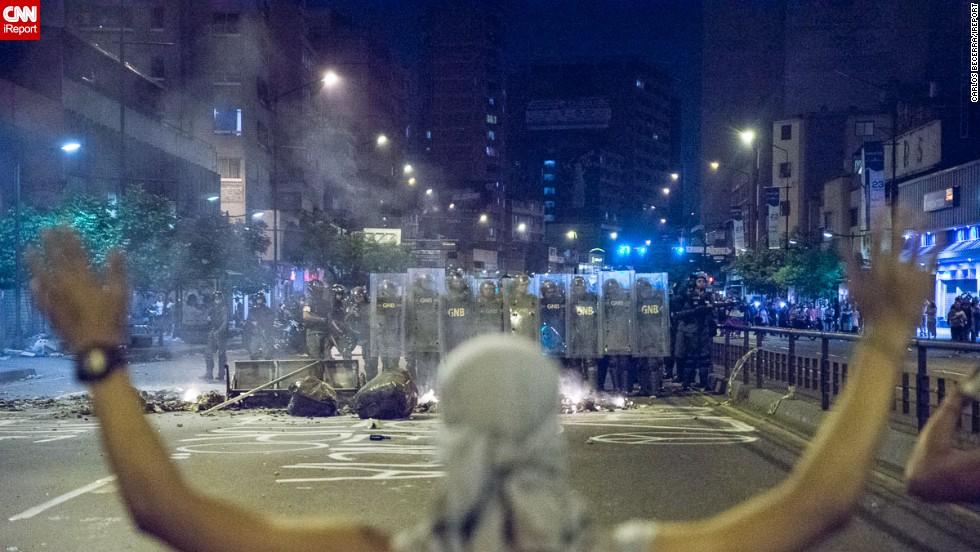 Un manifestante de rodillas y manos alzadas frente a la Guardia Nacional Bolivariana en la Av. Francisco de Miranda.