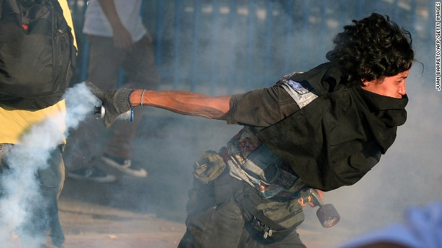 A student protester returns a tear gas cannister to riot police in Caracas on Saturday, February 15.