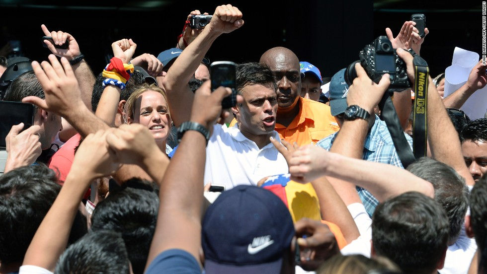Opposition leader Leopoldo Lopez greets supporters during a demonstration in Caracas on Wednesday, February 12. Lopez was charged with murder, terrorism and arson in connection with the protests, according to his party, Popular Will. Lopez denies the accusations, the party said in a statement.