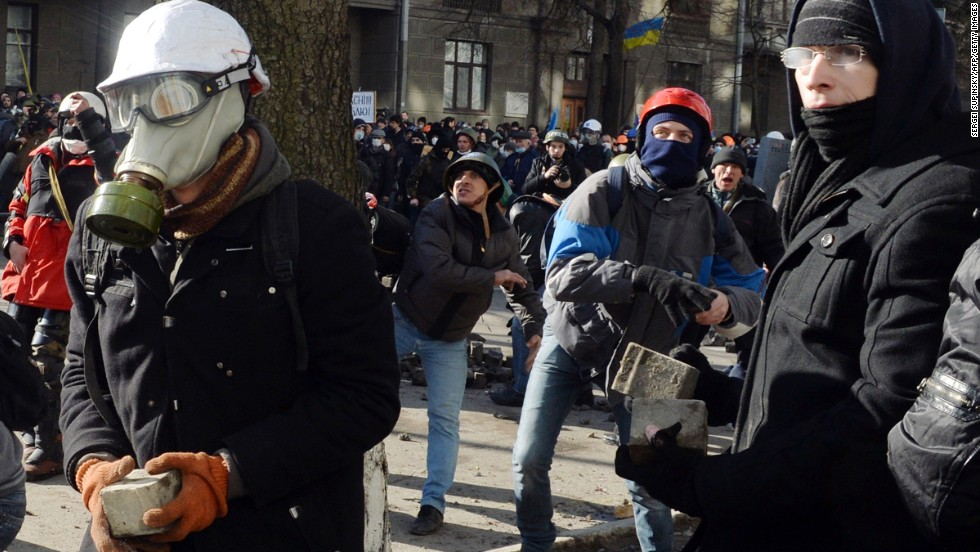 Protesters throw stones toward riot police in Kiev on February 18.