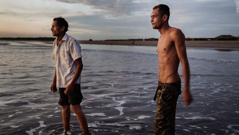 A father and son who are both sick with kidney disease wade in the water at the beach in Puerto Corinto, a coastal town near Chichigalpa.