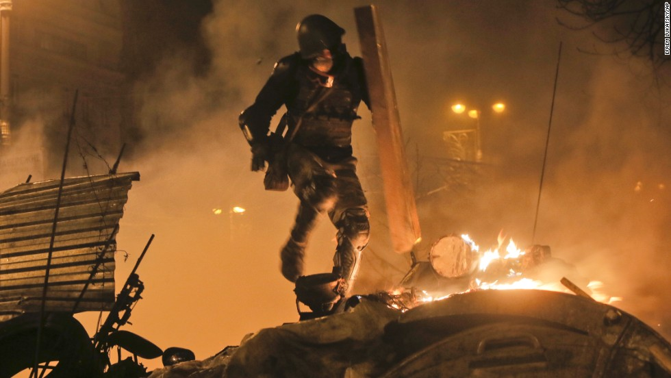 A protester runs during clashes with police in Kiev on Tuesday, February 18.