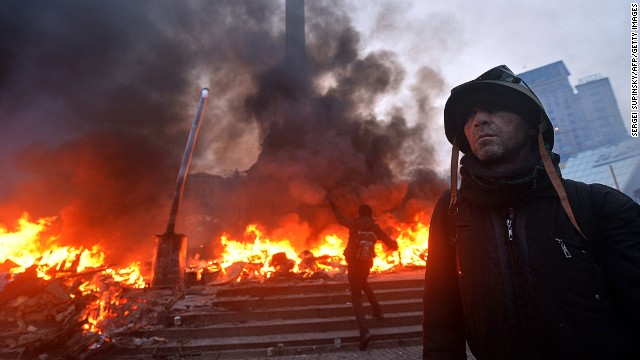 An anti-government protester wearing a helmet stands on Independence Square in Kiev during clashes with the police early on February 19, 2014.