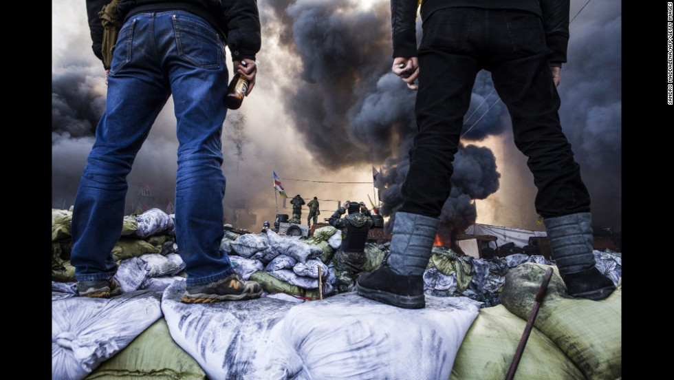 Protesters watch clashes in Kiev on February 18.