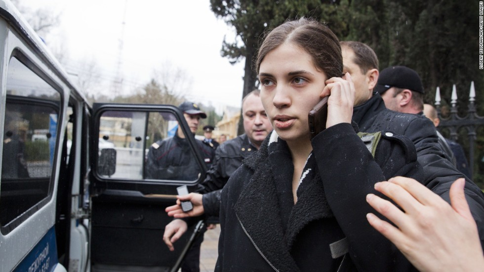 Tolokonnikova speaks on her cell phone as she is escorted to a police car on February 18.