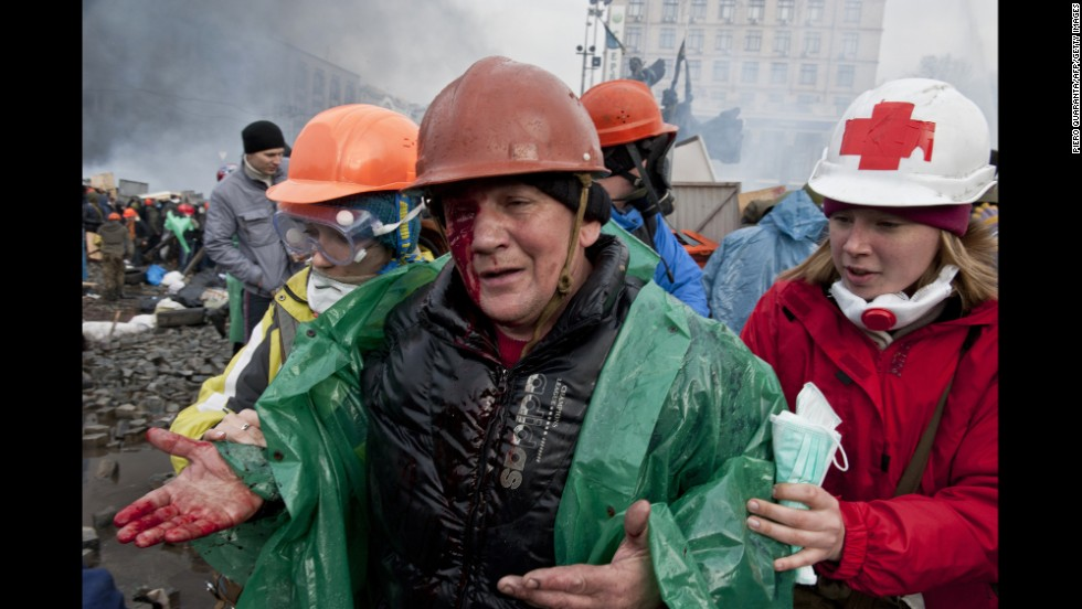 An injured protester is moved out during clashes with riot police in Kiev on February 19.