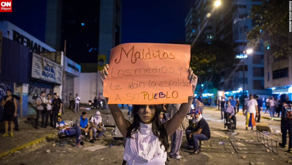 """Damned is the media that gives its people the cold shoulder,"" reads a <a href=""http://ireport.cnn.com/docs/DOC-1086189"">sign held by a student </a>protesting in Caracas on February 15. Protesters are upset because they say the national media is not reporting about the protests and the violence."