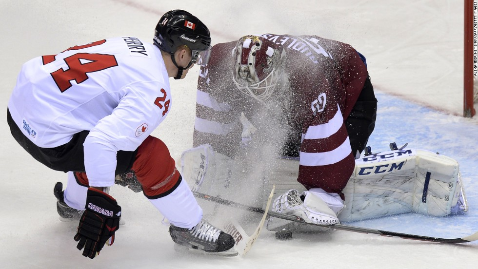 Canada's Corey Perry, left, sprays ice onto Latvia goalie Kristers Gudlevskis during their hockey game February 19.