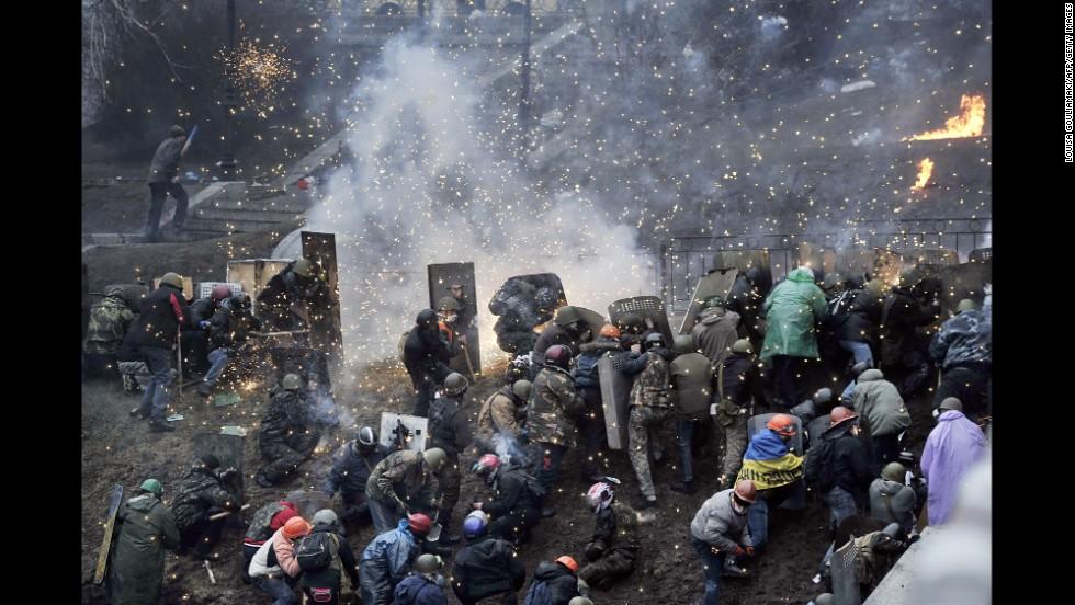 Fuegos explotan sobre los manifestantes cerca de Plaza de la Independencia , el 20 de febrero.