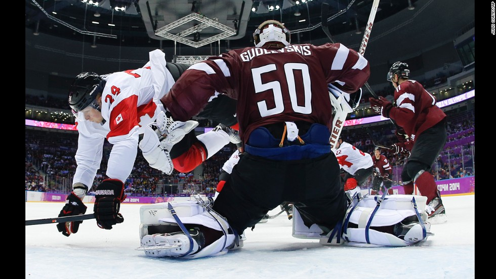Canada forward Corey Perry trips over Latvia goaltender Kristers Gudlevskis during the men's ice hockey quarterfinal on Wednesday, February 19.