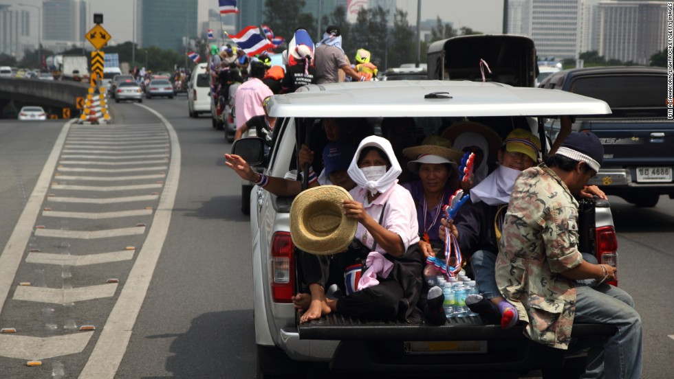 A convoy of trucks carrying protesters sets off for a demonstration at the defense ministry complex in Bangkok on February 19.