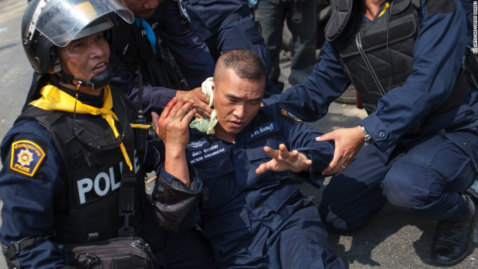 "Police officers assist a colleague who was injured by a grenade thrown by protesters in Bangkok on Tuesday, February 18. At least five people were killed and more than 70 were injured in clashes <a href=""http://www.cnn.com/2014/02/17/world/asia/thailand-protests/index.html"">during a police crackdown</a>."