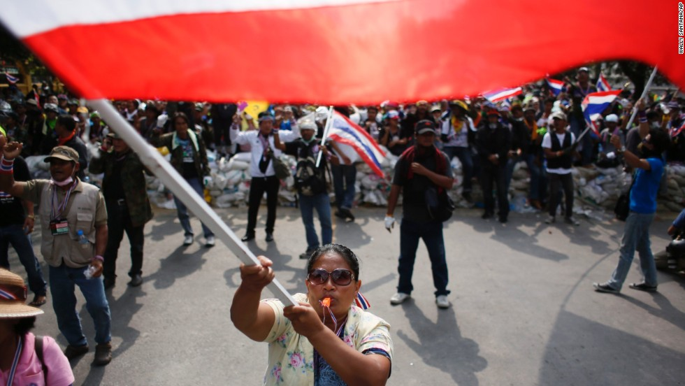 Protesters wave flags during a standoff with riot police in Bangkok on February 18.