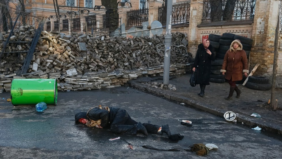 A wounded person lies on the ground during clashes in central Kiev on February 18.