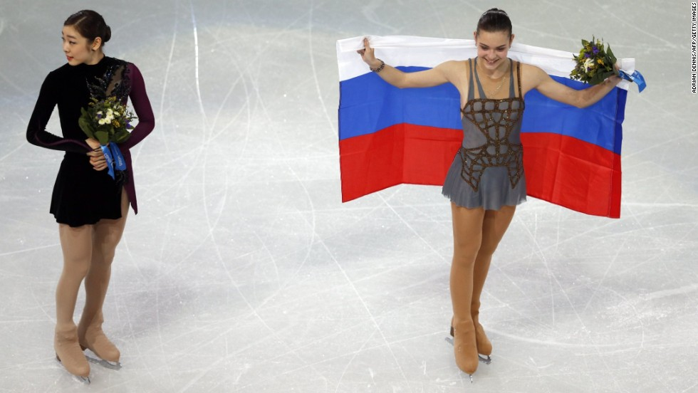 Gold medalist Adelina Sotnikova of Russia, right, and silver medalist Yuna Kim of South Korea take part in the flower ceremony after the women's free skating program in Sochi, Russia, on Thursday, February 20. Some are questioning the scores given to the skaters since Kim seemingly had a better overall performance.