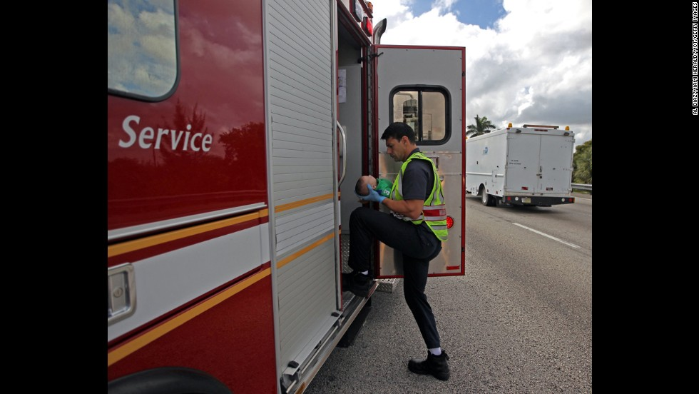 A paramedic transports the baby to the hospital.