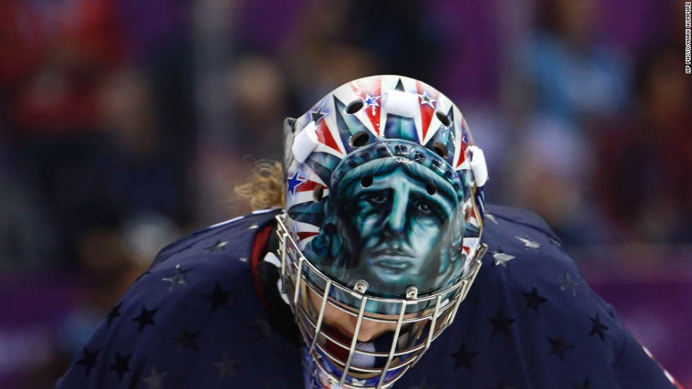 While U.S. hockey goalkeeper Jessie Vetter looks down during a break in play, her helmet reveals a scary version of Lady Liberty.