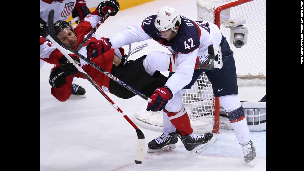 U.S. forward David Backes hits Canada's Patrick Sharp on February 21.