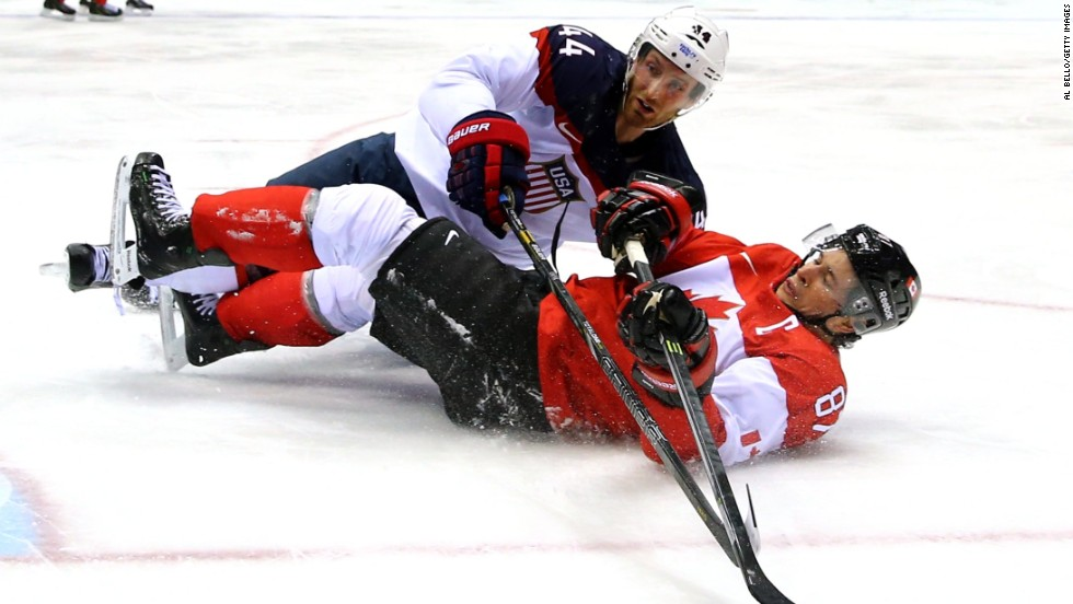 America's Brooks Orpik, top, and Canada's Sidney Crosby fall to the ice during their semifinal game.