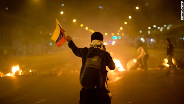 A Venezuelan protester waves a flag in front of a burning barricade in Caracas on Friday, February 21.