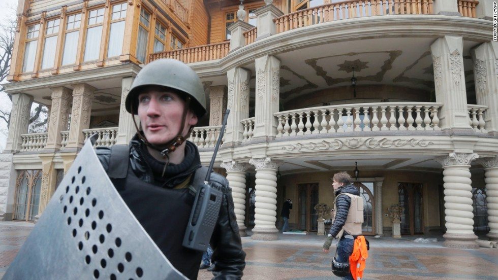A protester guards the entrance to Yanukovych's abandoned residence outside Kiev on February 22.
