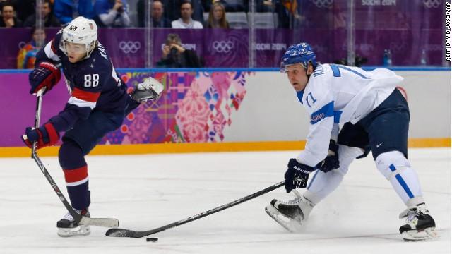 USA forward Patrick Kane breaks his stick while taking a shot on goal as Finland forward Leo Komarov defends Saturday.