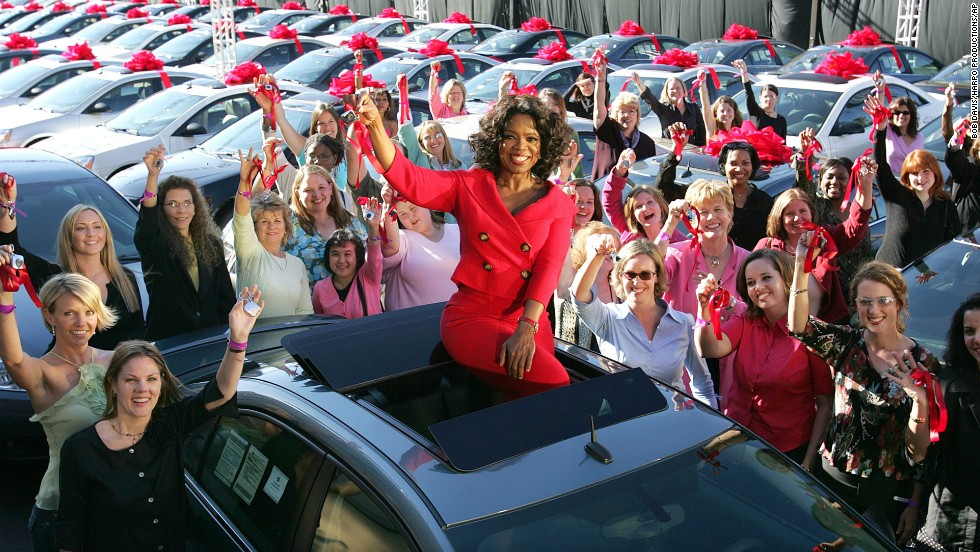 One of Chicago's most famous residents, Oprah Winfrey, sits atop a brand new car -- one of hundreds that she gave away to audience members in 2004 -- outside her Chicago studios. Winfrey moved her talk show to Chicago's West Loop in 1988, purchasing an 88,000-square-foot facility in the neighborhood, which was struggling at the time. She is now reportedly considering selling Harpo Studios, which helped revitalize the neighborhood.