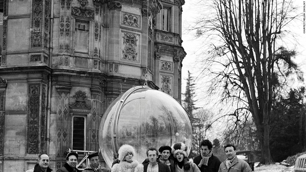 Here photographer Melvin Sokolsky, model Simone D'Aillencourt, and crew pose beside the bubble in Paris.