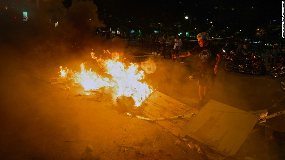 A man stands next to a burning street barricade during a protest against the Venezuelan government in Caracas on Monday, February 24.