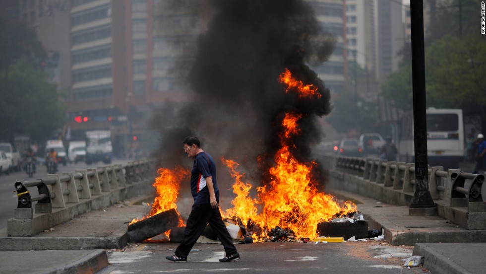 A pedestrian moves past a burning barricade blocking a highway in Caracas on February 24.