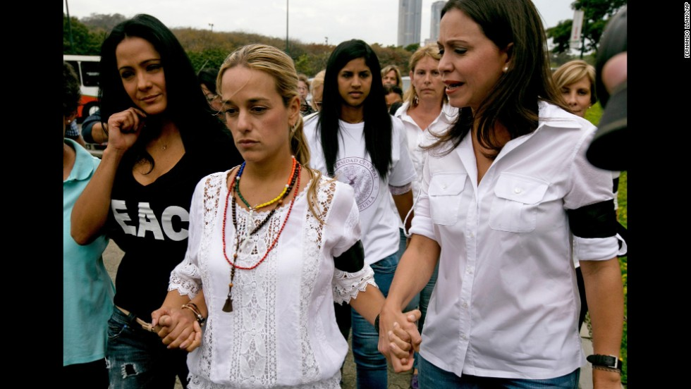 Lilian Tintori de Lopez, the wife of jailed opposition leader Leopoldo Lopez, center, walks hand in hand with actress Norkys Batista, left, and lawmaker Maria Corina Machado as they arrive for a news conference in Caracas on February 24.