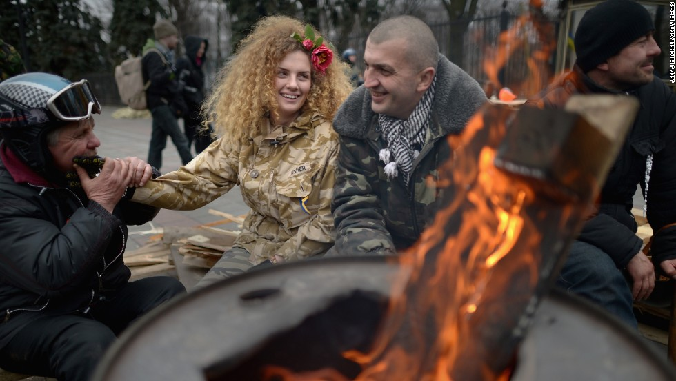 "FEBRUARY 26 - KIEV, UKRAINE: Anti-Yanukovych demonstrators sit by a brazier outside the Ukrainian parliament in Kiev. The<a href=""http://edition.cnn.com/2014/02/26/world/europe/ukraine-politics/index.html?hpt=hp_t1""> country's interim leaders are due to form a unity government</a>, as UK and U.S. foreign ministers and the IMF meet to discuss emergency financial assistance for the country."