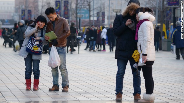 Pedestrians in Beijing use their mobile phones as they wait to cross the street.
