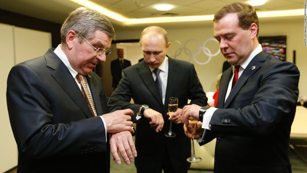 "From left, International Olympic Committee President Thomas Bach, Russian President Vladimir Putin and Russian Prime Minister Dmitry Medvedev look at their watches before the <a href=""http://www.cnn.com/2014/02/23/world/gallery/olympic-closing-ceremony/index.html"">closing ceremony</a> of the Winter Olympics on Sunday, February 23, in Sochi, Russia."