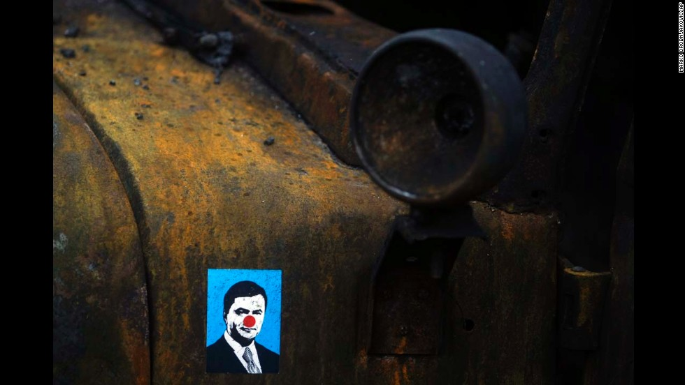 "A sticker depicting Ukrainian President Viktor Yanukovych is placed on a burned military truck in Kiev, Ukraine, on Sunday, February 23. Following deadly clashes between anti-government protesters and security forces in Kiev, the country's Parliament <a href=""http://www.cnn.com/2014/02/24/world/gallery/ukraine-in-transition/index.html"">voted to oust Yanukovych</a> and start shaping a new government."