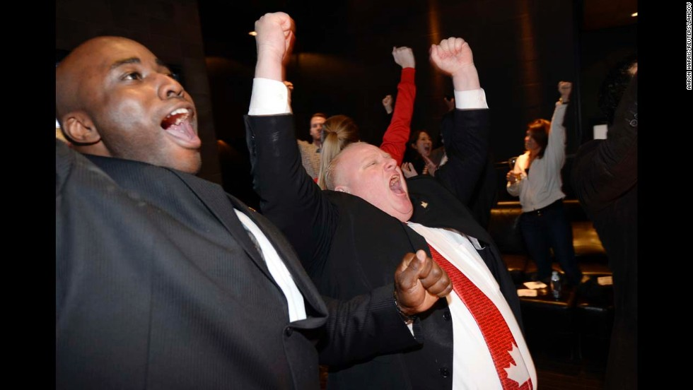 "Toronto Mayor Rob Ford, right, celebrates as he watches the televised broadcast of Canada's Olympic win over the United States in the men's hockey semifinals Friday, February 21. Canada went on to <a href=""http://www.cnn.com/2014/02/23/sport/olympics-sochi-canada-final-day/index.html"">win the gold medal</a>."