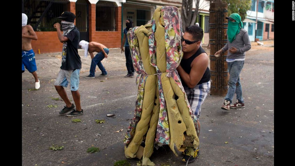 "A demonstrator protects himself with an old mattress during clashes with police in Valencia, Venezuela, on Saturday, February 26. For weeks, anti-government protesters -- unhappy with the economy and rising crime -- <a href=""http://www.cnn.com/2014/02/18/world/gallery/venezuela-protests/index.html"">have been fighting </a>with security forces in the country."