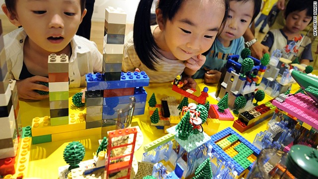 (FILES) - Japanese children look at their work made by LEGO bricks as part of the Dream City building event produced by LEGO education in Tokyo on August 16, 2009. Danish toy maker Lego on September 5, 2013 reported an 18-percent rise in first-half net profit as revenue grew 13 percent, fuelled by growth in Asia as developed markets stalled. AFP PHOTO/Kazuhiro NOGIKAZUHIRO NOGI/AFP/Getty Images