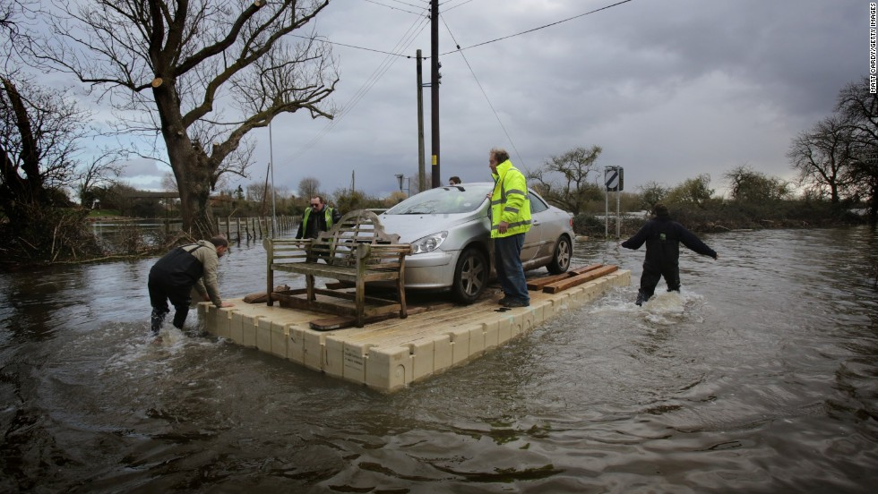 Volunteers use a pontoon to move a car that has been cut off by floodwaters in Somerset, England, on Thursday, February 27.