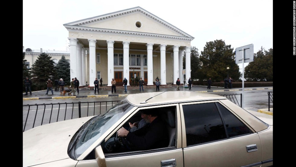 Armed men stand guard in front of a building near the Simferopol airport on February 28.