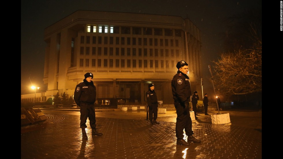 Police stand guard outside the Crimea regional parliament building Thursday, February 27, in Simferopol. Armed men seized the regional government administration building and parliament in Crimea.