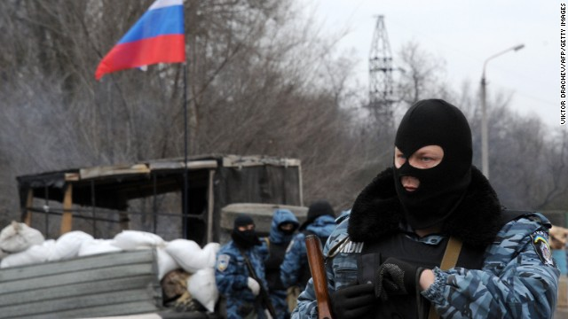 Armed masked men who call themselves members of Ukraine's disbanded elite Berkut riot police force stand at their checkpoint under a Russian flag on a highway that connect Black Sea Crimea peninsula to mainland Ukraine near the city of Armyansk, on February 28, 2014. The spiralling tensions in a nation torn between the West and Russia took today a severe new turn when Ukraine's interim president Oleksandr Turchynov accused Russian soldiers and local pro-Kremlin militia of staging raids on Crimea's main airport and another base on the southwest of the peninsula where pro-Moscow sentiments run high.