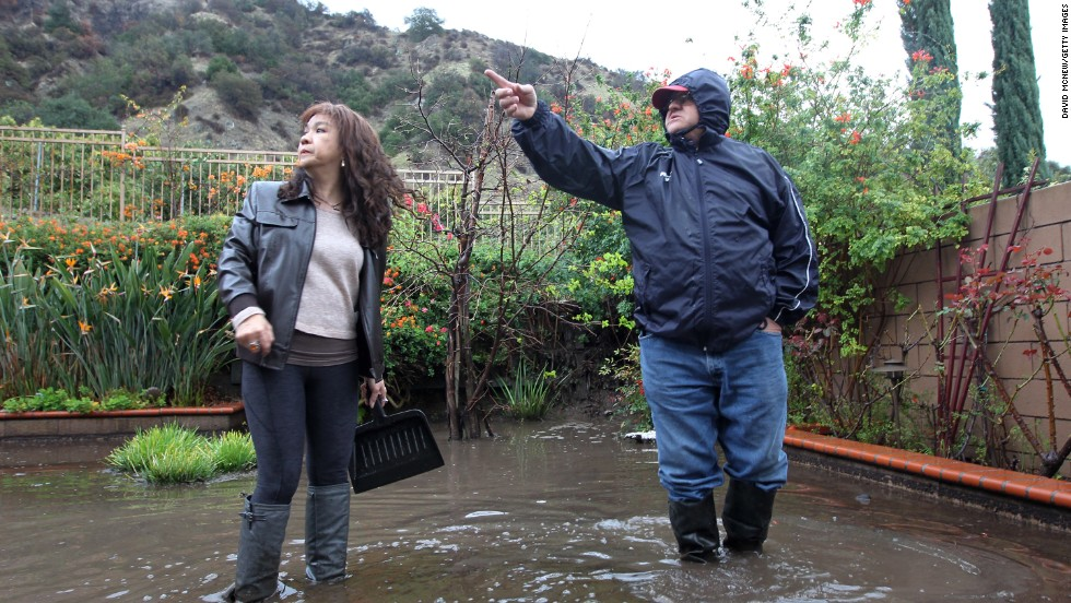 Mari Poblete, left, and neighbor Lorenzo Tatone look at hillsides from which ash, water and mud flow through her yard below on February 28.